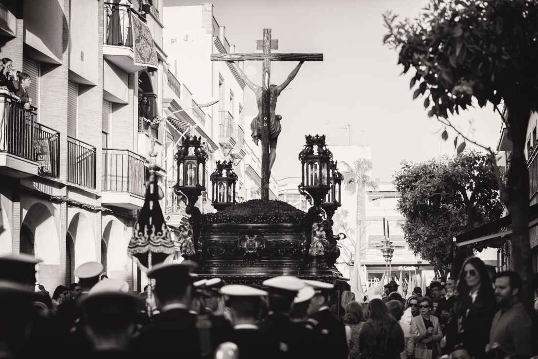 greyscale photo of group of people carrying crucifix